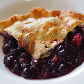 A picture of a slice of blueberry pie.