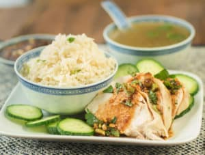 A picture of Weeknight Hainanese Chicken Rice with cucumbers, cilantro, a soy dipping sauce and a delicious broth for soup