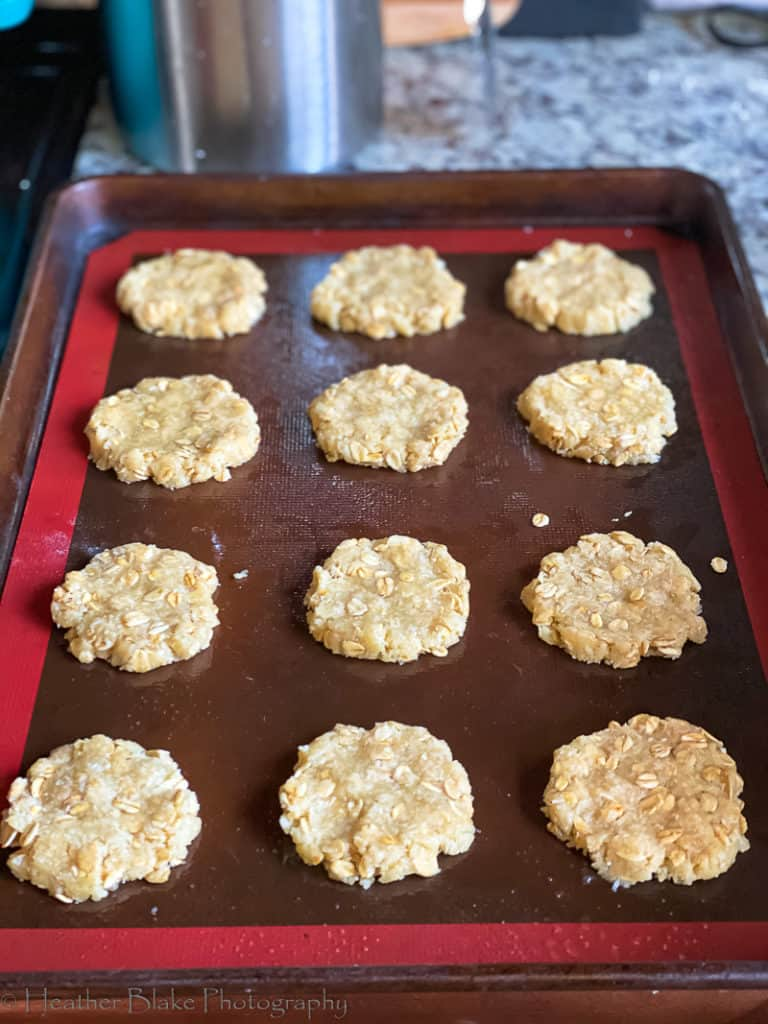 A picture of Anzac Biscuits that are flattened out before going into the oven.