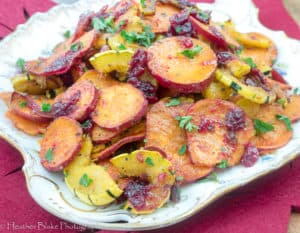 A picture of Roasted Squash and Sweet Potatoes with Cranberries on a plate ready for Service.