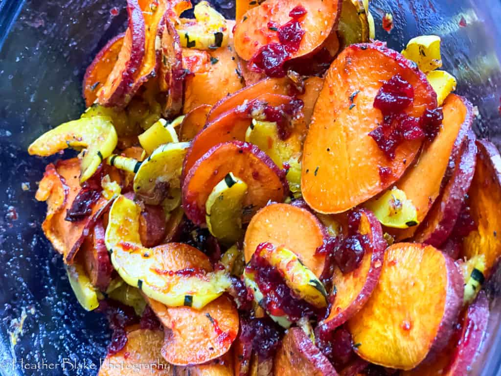 A picture of roasted squash and sweet potatoes tossed with homemade cranberry sauce.