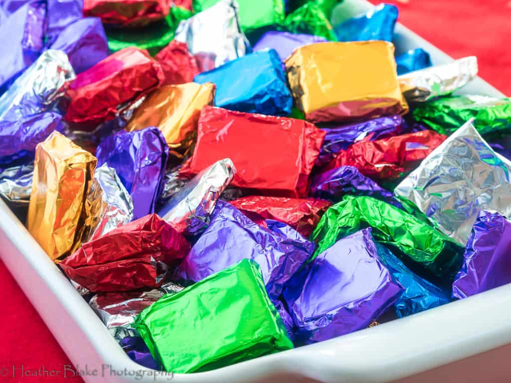 A picture of black sea salt caramels wrapped up in colorful foil wrappers.