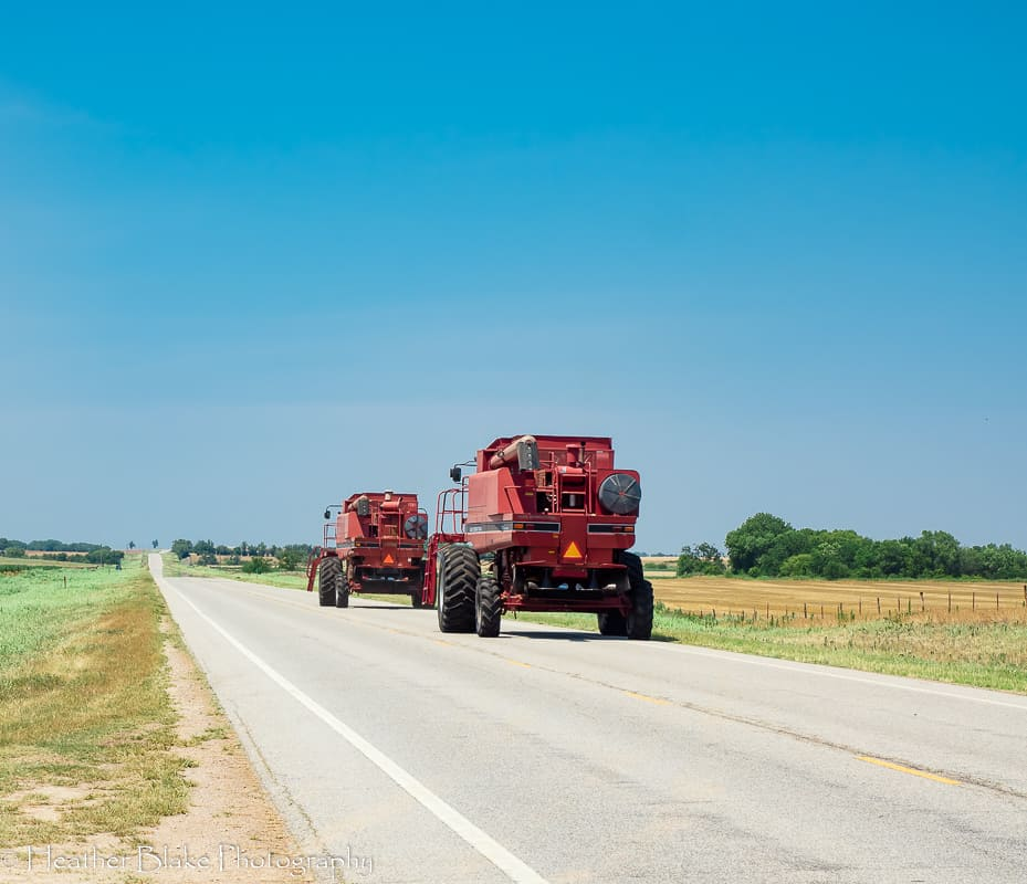 A picture of gigantic red tractors driving down a back road in Kansas.