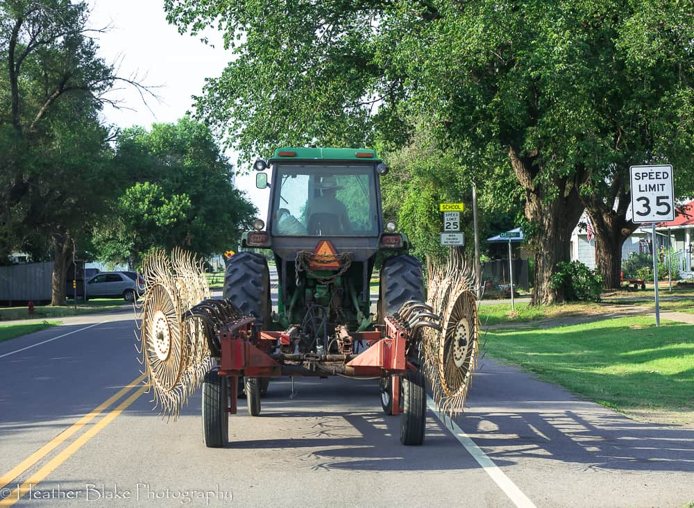 An old looking tractor driving down the road in a small town in Oklahoma.